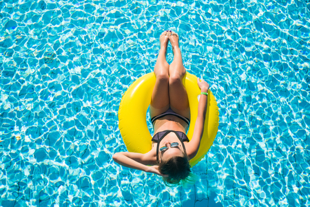 Happy young woman in bikini with rubber inflatable float, playing and having a good time at water fun park pool, on a summer hot day