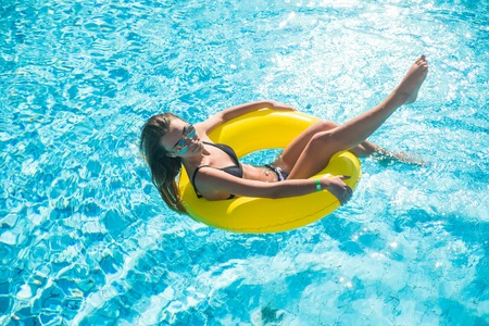 Woman relaxing on donut lilo in the pool water in hot sunny day.