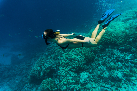 Young girl at snorkeling in the tropical water.