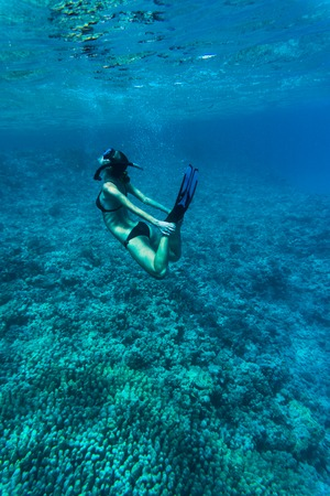 Underwater image of a young lady snorkeling and diving in a tropical sea