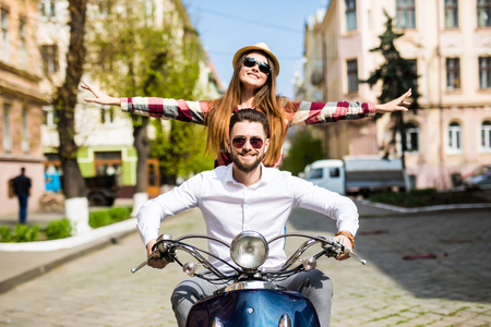 Couple in love riding a motorbike , Handsome guy and young sexy woman travel . Young riders enjoying themselves on trip. Adventure and vacations concept. Standard-Bild