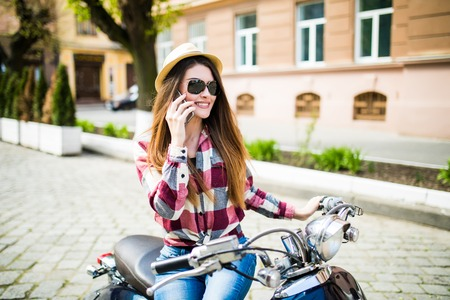 motobike: Young woman in hat using smartphone while sitting on motorbike.