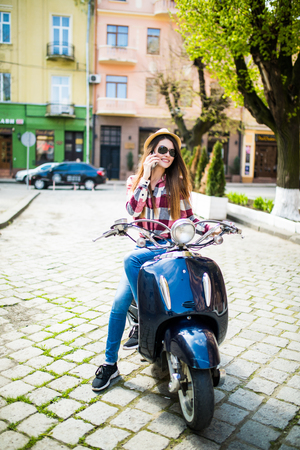 Jeune femme habillée décontracté assis sur scooter et de parler sur le téléphone. téléphone Banque d'images - 77275376