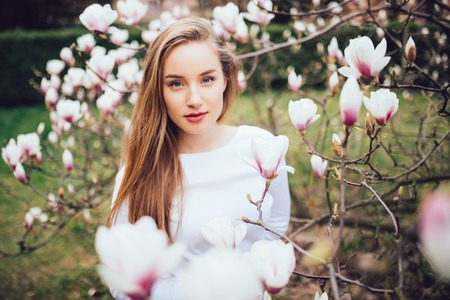 lovely girl standing near Magnolia blossoming flowers, stands in white pink dress a small smile smiling near magnolia tree Stock Photo