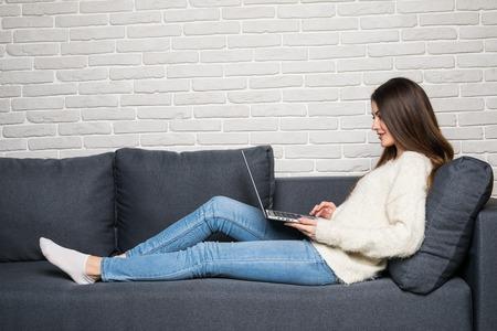 집에서 거실에서 그녀의 노트북을 사용하여 소파에 앉아 여자