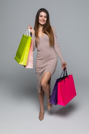 compras compulsivas: Shopping woman walking and holding bags - isolated over grey