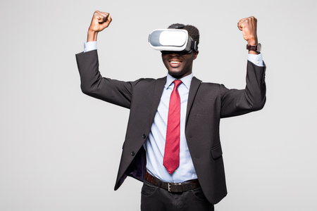 African employee wearing formal suit and goggles, experiencing virtual reality, stretching his arms up like win game. Black man playing video games using oculus Stock Photo