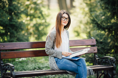 serious young, beautiful girl holding an open book, read background summer park