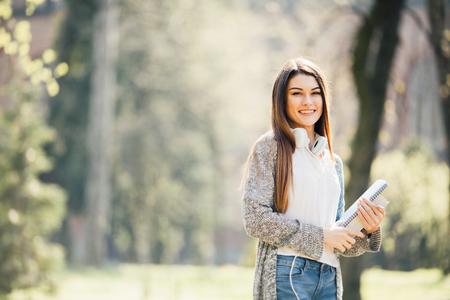 公園でノートブックを保持して立っているバックパックと幸せの魅力的な若い女性