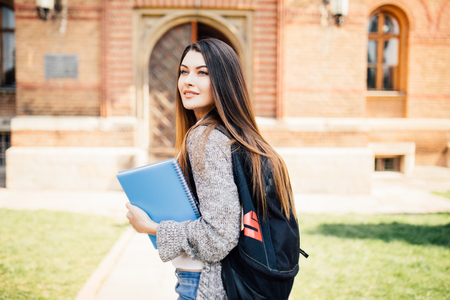 American university student smiling with coffee and book bag on campus with print space Stock Photo
