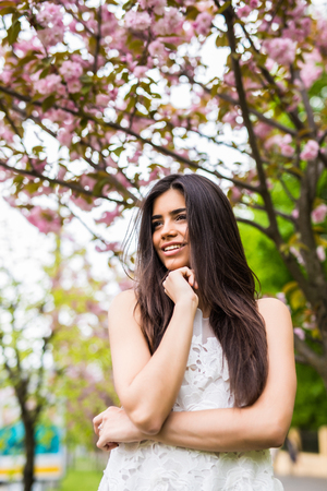 Beautiful young woman enjoying sunny day in park during cherry blossom season on a nice spring day