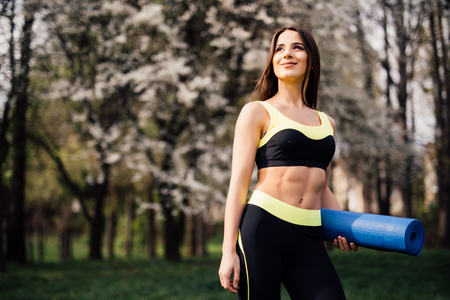 Pilates Girl with Yoga Mat Standing Outdoor in Nature - Fit woman with exercise accessory in summertime landscape