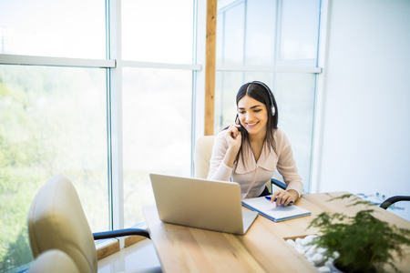 Happy young woman sitting and working with laptop using headset in office Stock Photo