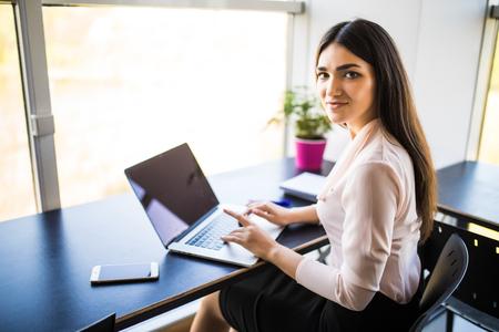 concentré à la jeune femme belle jeune femme utilisant son ordinateur portable alors qu & # 39 ; il était assis dans un fauteuil à son lieu Banque d'images