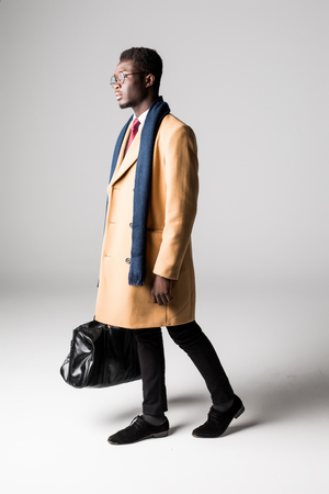 Black businessman with bag in coat on white Stock Photo