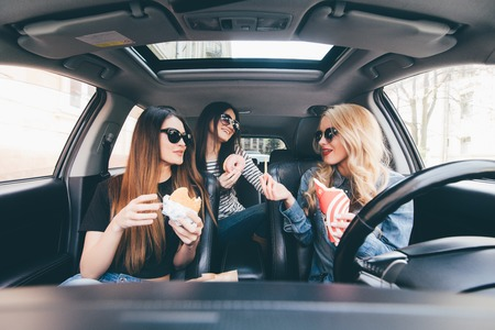 Three young women drive a car, speaking each other and eating a fast food in a car in traffic Stockfoto