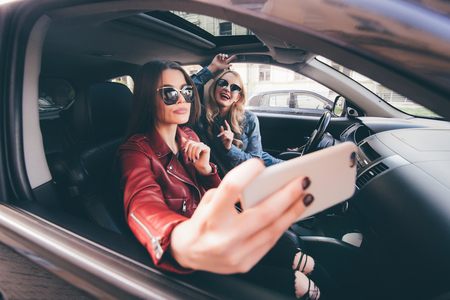 Group of girls having fun with the car. Taking selfie while driving Stock Photo