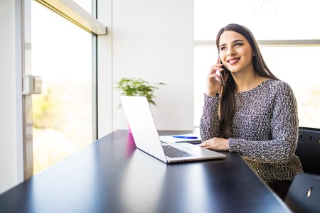 Freelancer female working and talking on the phone and browsing in a laptop at home or office