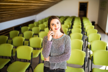 A beautiful business woman sitting alone in an auditorium