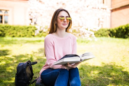 against background of green meadow sat young, charming girl - student reads book Stock Photo