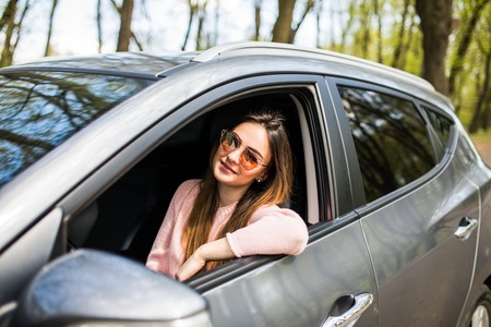 Smiling beautiful brunette woman driving a car