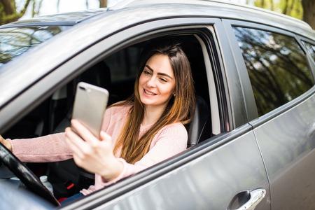 woman hand holding smartphone on window car Foto de archivo
