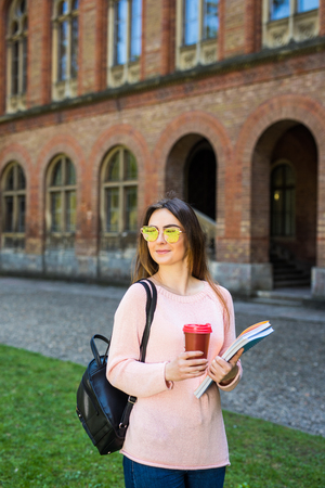 nerdy: University student smiling with coffee and book bag on campus
