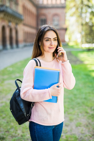 Girl college student sitting outside building and taking a selfie Stock Photo