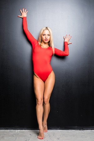 Young blonde slim woman gymnastic dancer in red body isolated on black