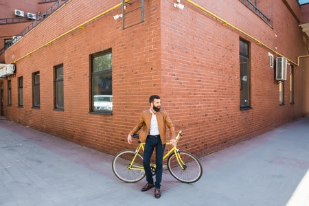 oldened: Young handsome man with a beard against the backdrop of a brick wall sits on a bicycle