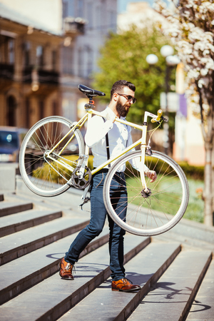 Hipster man in sunglasses carrying on his shoulder bike on street stairs. Young handsome man with beard holding bike on his right arm.