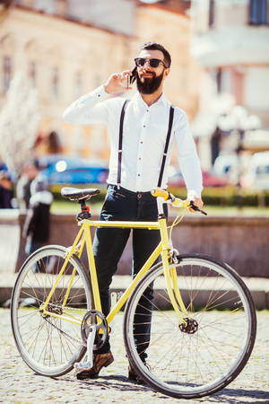 Cheerful young man with beard talking on the mobile phone and smiling while standing near his bicycle.