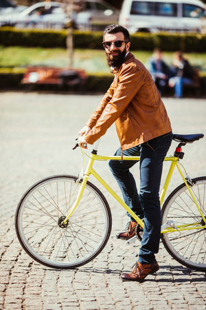 Full length of confident young bearded man adjusting eyewear and looking at camera while sitting on his bicycle outdoors Stock Photo