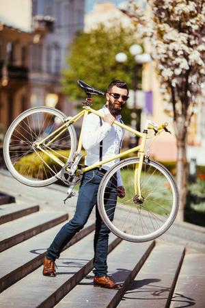 bajando escaleras: Hipster hombre en gafas de sol llevando en su hombro bicicleta en las escaleras de la calle. Joven apuesto hombre con barba sosteniendo bicicleta en su brazo derecho. Foto de archivo