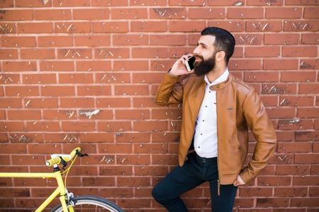 Young hipster man checking his cellphone with his fixed bicycle on the wall