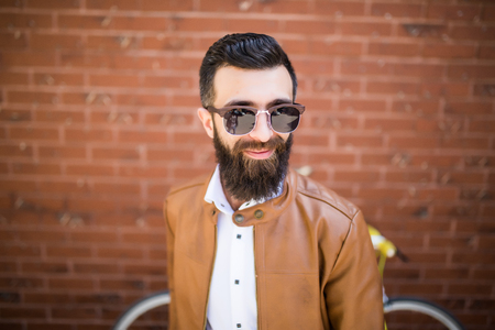 reggicalze: portrait of a brutal bearded man on brick wall background. Young stylish hipster posing in the street.