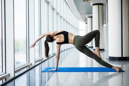 Übendes Yoga der Frau in einem panoramischen Fensterhintergrund