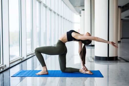Beautiful yoga woman practice in a big window hall background.