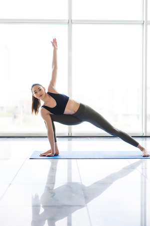 ardha: Young woman practicing yoga with panoramic windows in the background. Freedom concept. Calmness and relax, woman happiness. Stock Photo