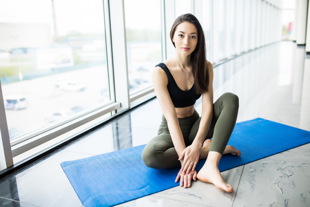 Attractive woman sitting relax in the mat on floor after yoga training in gym Banco de Imagens