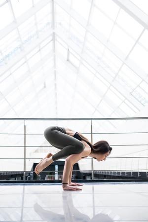 ardha: Beautiful yoga woman practice in a big window hall background.