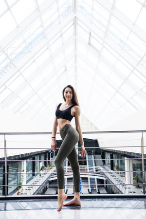 Full length side view portrait of beautiful young woman before training in luxury fitness center