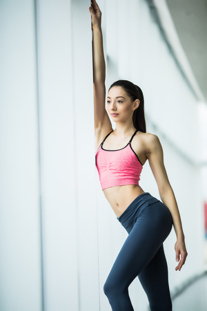 Stretching after great workout. Young beautiful young woman in sportswear doing stretching while standing in front of window at gym Stock Photo