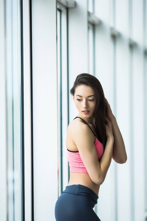 beautiful girl standing in the gym at the window and possing Фото со стока