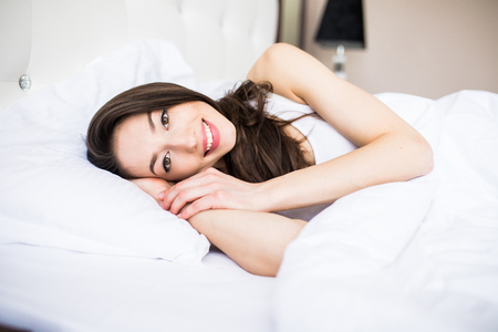 Happy woman lying in bed at home in the bedroom Stock Photo