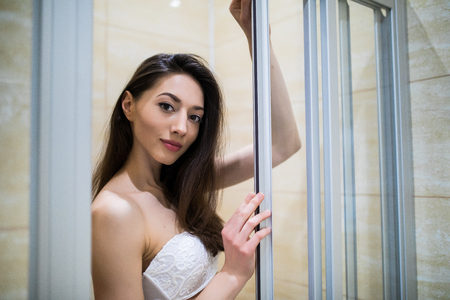 Portrait smiling young woman in bethroom before shower Stock Photo