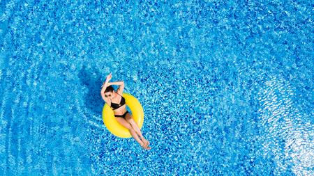 日焼けを楽しんでいます。休暇の概念。大きなスイミング プールで黄色の空気マットレスの上のビキニでスリムな若い女性の平面図です。 写真素材