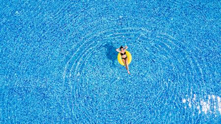 Vrouw ontspant in het zwembad in zonnige dag in geel opblaasbare ring Stockfoto