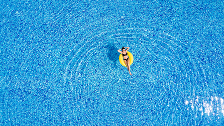 Woman relax in the pool in sunny day in yellow inflatable ring