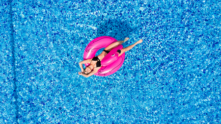 Jong en sexy meisje met plezier en lachen in het zwembad op een opblaasbare roze flamingo in een badpak in de zomer van bovenaf